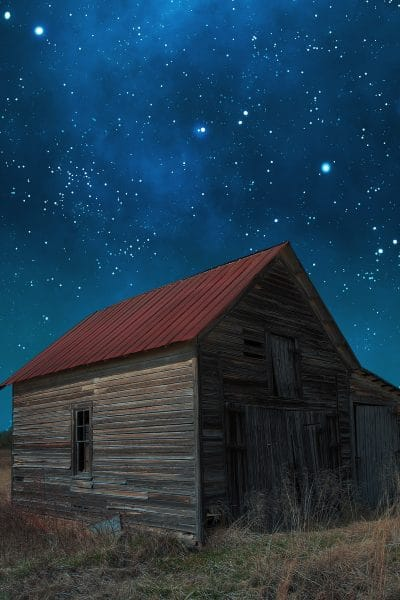 A starry night with an old barn in the foreground
