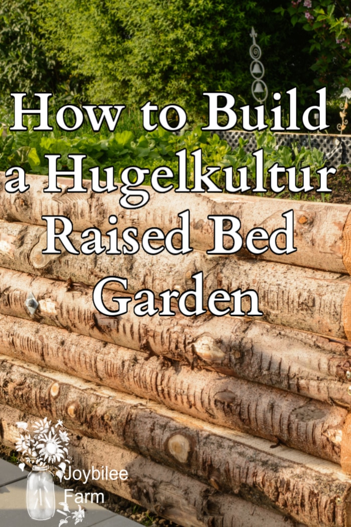 """side of a raised wooden bed with text """"how to build a hugelkultur raised bed garden"""""""