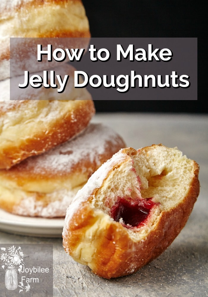 A stack of jelly doughnuts on a plate in front of a half eaten jam filled doughnut