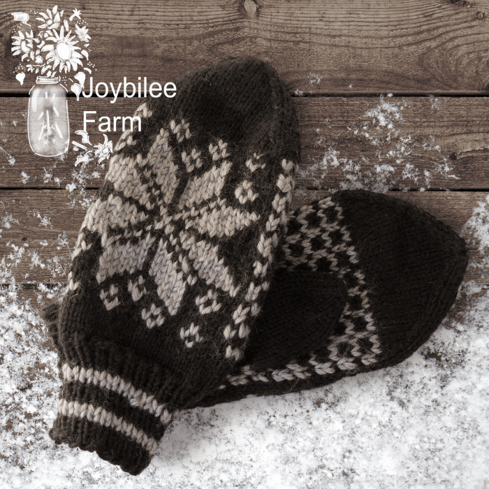 grey knit mittens on a wood and snow background
