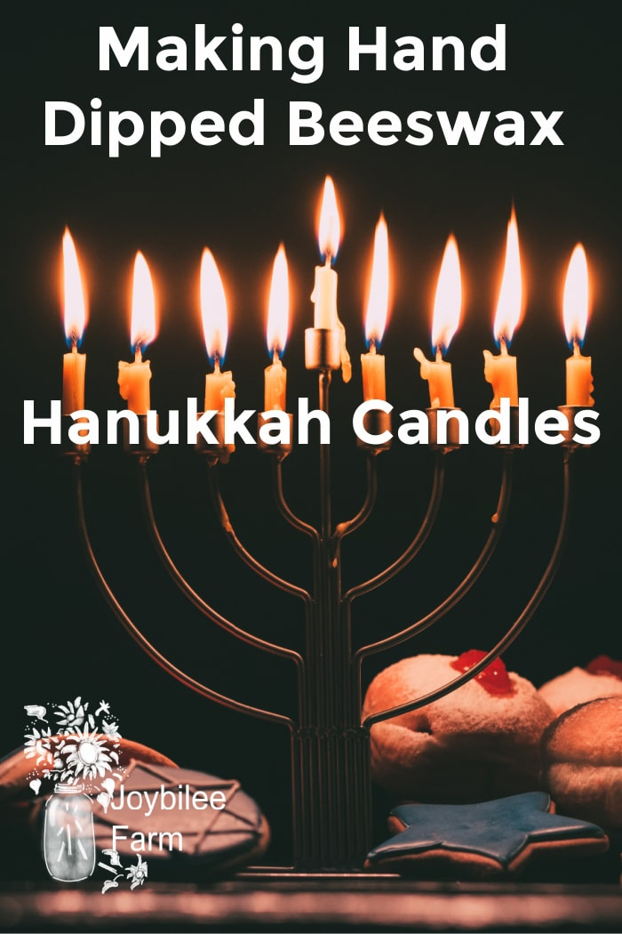 lit hanukkah menorah on a dark background, with donuts and cookies at the base