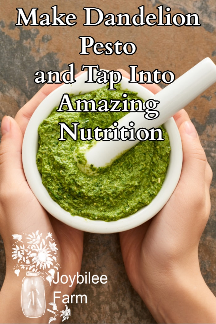 fresh pesto in a white mortar and pestle, held by two hands.