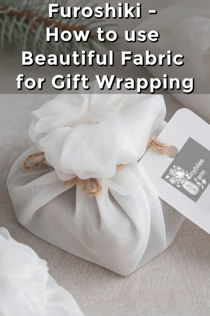 Christmas presents wrapped with white furoshiki fabric