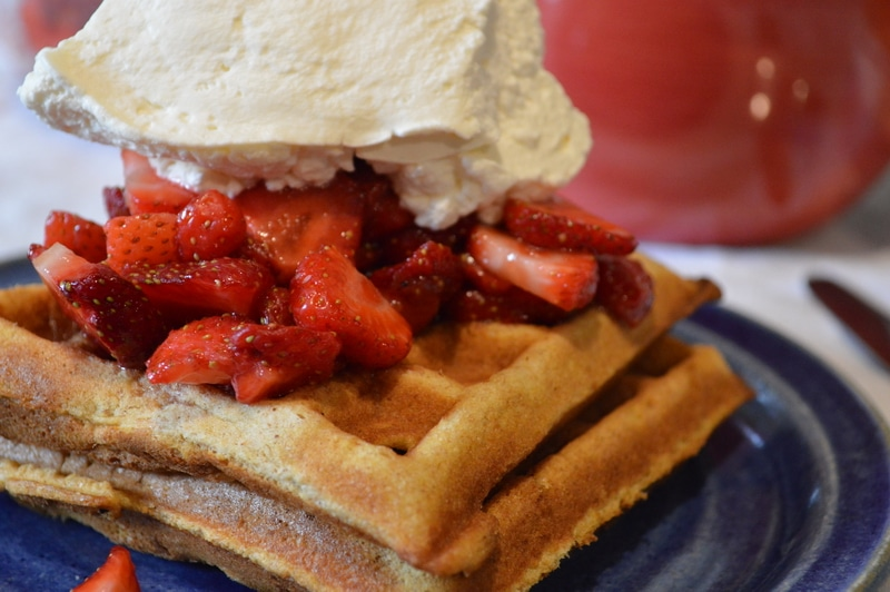 Fresh made waffles with strawberries and whipped cream.