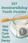 Tooth powder with a bamboo toothbrush sitting on top