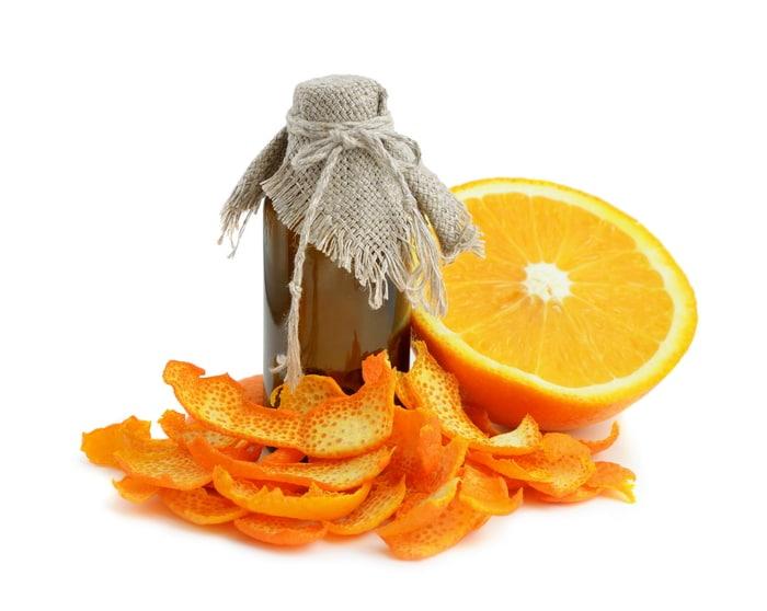 Dried orange peels, a fresh sliced orange and a bottle of homemade orange extract