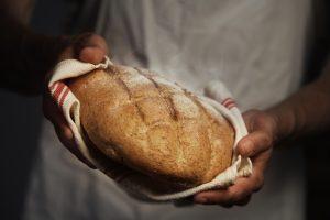 A baker holding fresh sourdough in a white towel