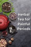 A teapot and dried herbs on a slate background