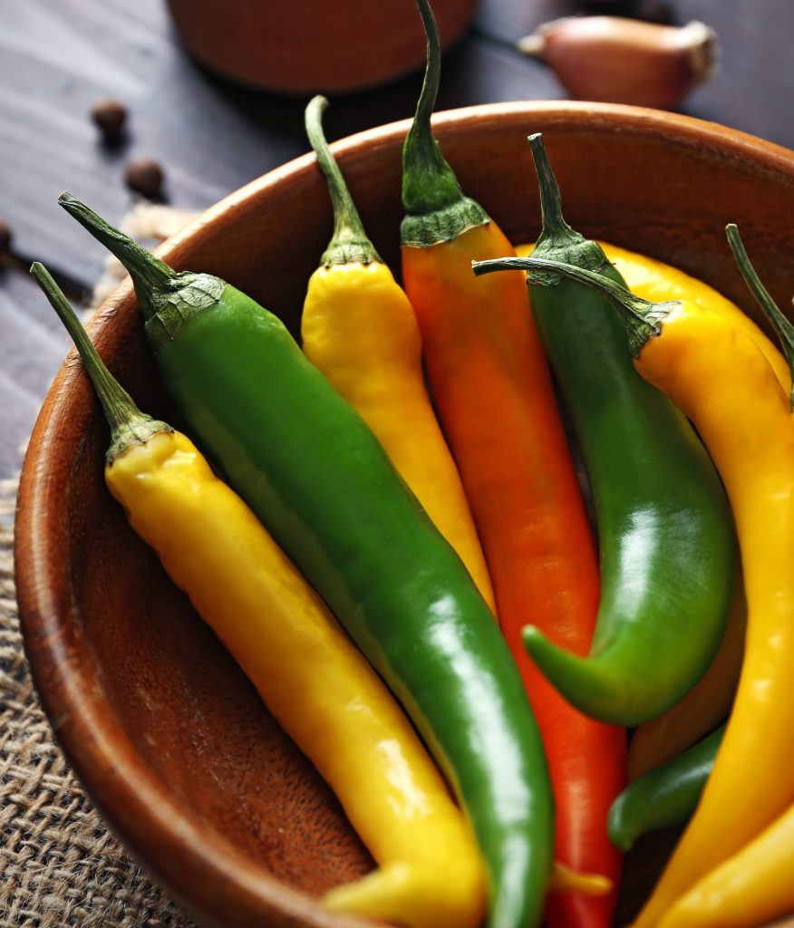 A wooden bowl with orange, yellow and green hot peppers