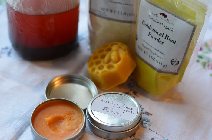 Ingredients for goldenseal, myrrh, and frankincense salve with finished salve in foreground.