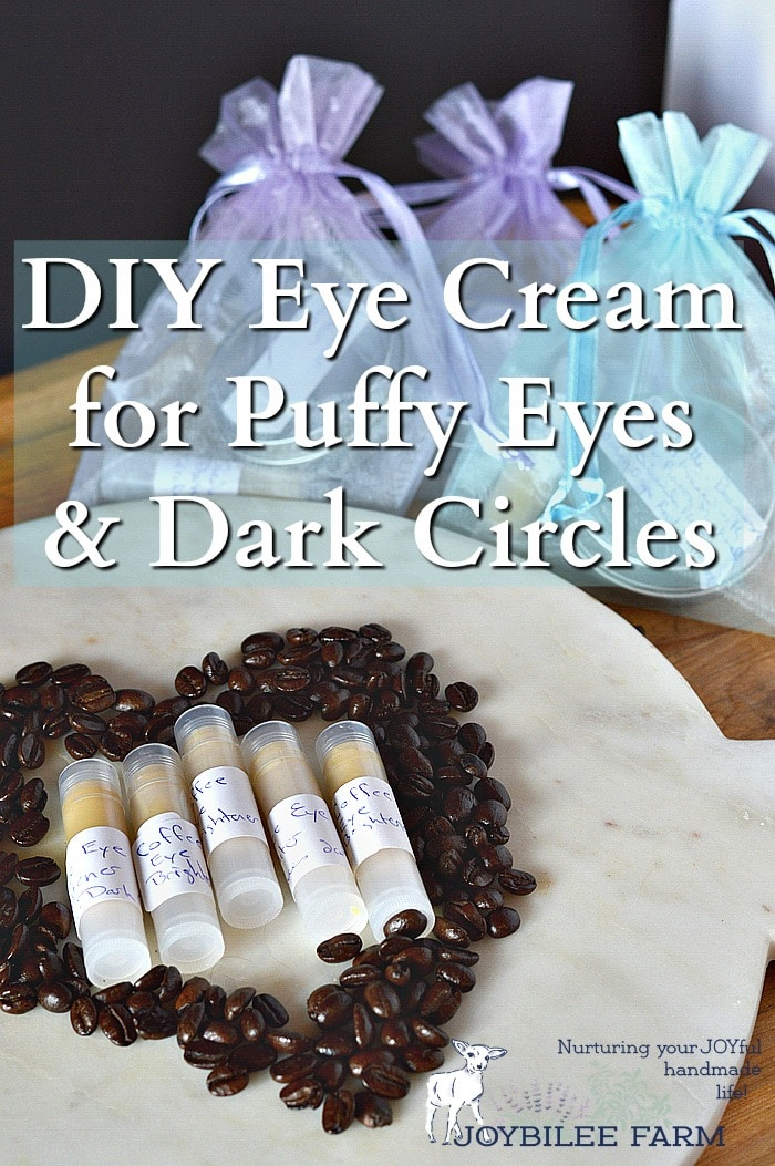 Coffee eye cream in tubes on a plate surrounded with coffee beans, and with gift bags in the background.