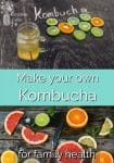 Citrus slices on a board by a glass of kombucha