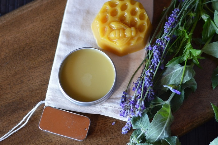healing Salves sitting by fresh lavender and other herbs