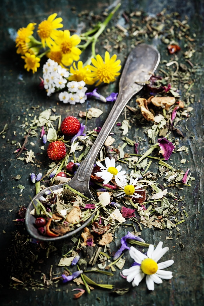 dry herbs and flowers with a silver spoon