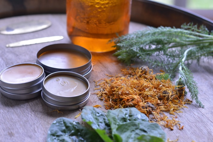 Homemade salves sitting by natural herbs