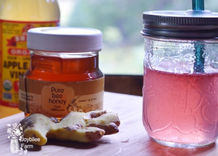 ginger and honey on a table with a canning jar full of homemade switchel