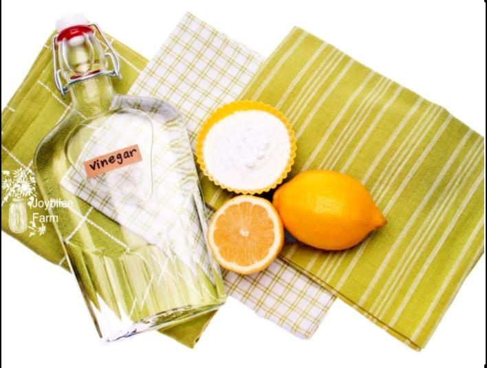 a bottle of vinegar and lemons on a towel used to make lemon vinegar cleaner