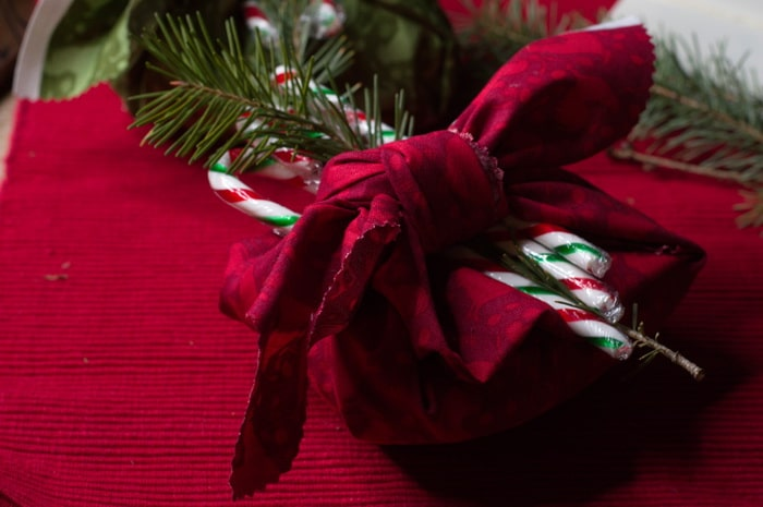 gift wrapped with fabric, a sprig of pine and a candy cane