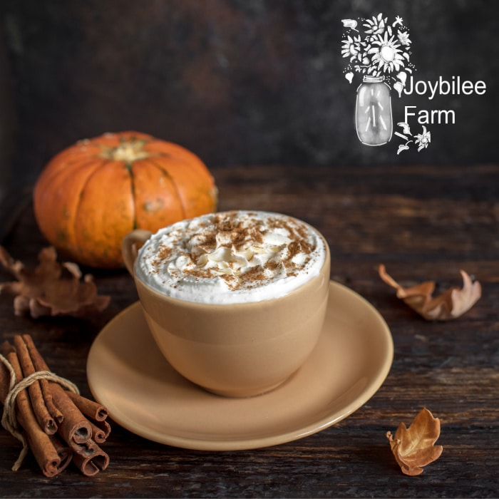 A pumpkin spice latte on a dark wooden table with a pumpkin in the background